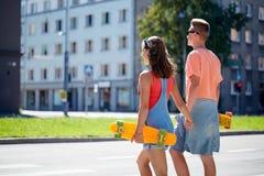 Εφηβικό ζεύγος με skateboards στη διάβαση πεζών πόλεων Στοκ Φωτογραφίες