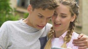 Εφηβικό ζεύγος που κάνει τα πρόσωπα, που παίρνουν selfie, app στο smartphone για την κατοχή της διασκέδασης απόθεμα βίντεο