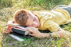 Εφηβικό να βρεθεί και ύπνος στη χλόη με το βιβλίο Στοκ εικόνες με δικαίωμα ελεύθερης χρήσης