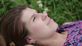 Εφηβικό ρομαντικό κορίτσι ομορφιάς που βρίσκεται στην κινηματογράφηση σε πρώτο πλάνο χλόης Πρότυπο κορίτσι Brunette με τα πράσινα φιλμ μικρού μήκους