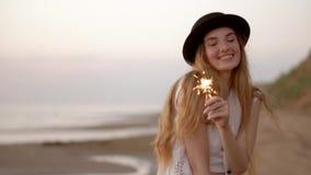 Εφηβικό όμορφο κορίτσι με τα sparklers στην παραλία στο ηλιοβασίλεμα φιλμ μικρού μήκους