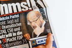 Εφημερίδα ανάγνωσης ατόμων που υποβάλλει έκθεση για την εκλογή της Άνγκελα Μέρκελ μέσα Στοκ Εικόνες