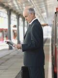 Εφημερίδα ανάγνωσης επιχειρηματιών στον κενό σταθμό τρένου Στοκ Φωτογραφία