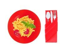 Εύγευστα ζυμαρικά με την ντομάτα και βασιλικός στο κόκκινο πιάτο που απομονώνεται Στοκ φωτογραφία με δικαίωμα ελεύθερης χρήσης