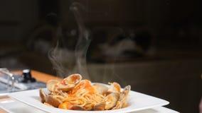 Εύγευστα ιταλικά ζυμαρικά με τα μαλάκια vongole και σάλτσα κρέμας έτοιμη να εξυπηρετηθεί Άσπρος ατμός Ιταλική έννοια πιάτων φιλμ μικρού μήκους