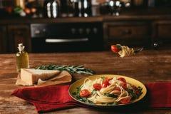 εύγευστα ιταλικά ζυμαρικά με τις ντομάτες και arugula στο πιάτο στον πίνακα με την παρμεζάνα Στοκ Εικόνες