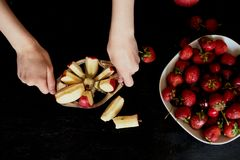 Εύγευστα και juicy φρούτα, κόκκινα στο μαύρο υπόβαθρο Με τα σταγονίδια νερού Κεράσι Apple και φράουλα Περικοπή χεριών γυναικών `  Στοκ φωτογραφία με δικαίωμα ελεύθερης χρήσης