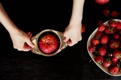 Εύγευστα και juicy φρούτα, κόκκινα στο μαύρο υπόβαθρο Με τα σταγονίδια νερού Κεράσι Apple και φράουλα Περικοπή χεριών γυναικών `  Στοκ Εικόνα