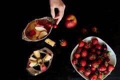 Εύγευστα και juicy φρούτα, κόκκινα στο μαύρο υπόβαθρο Με τα σταγονίδια νερού Κεράσι Apple και φράουλα Στοκ Εικόνα