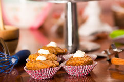 Εύγευστα καφετιά χρωματισμένα muffins με τη σάλτσα καραμέλας και το κάλυμμα κρέμας, ζωηρόχρωμο κέικ στο υπόβαθρο, έννοια ζύμης Στοκ εικόνες με δικαίωμα ελεύθερης χρήσης