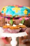 Εύγευστα καφετιά χρωματισμένα muffins με τη σάλτσα καραμέλας και το κάλυμμα κρέμας, ζωηρόχρωμο κέικ στο υπόβαθρο, έννοια ζύμης Στοκ Εικόνα