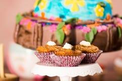Εύγευστα καφετιά χρωματισμένα muffins με τη σάλτσα καραμέλας και το κάλυμμα κρέμας, ζωηρόχρωμο κέικ στο υπόβαθρο, έννοια ζύμης Στοκ Εικόνες