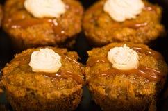 Εύγευστα καφετιά χρωματισμένα muffins που παρατάσσονται με το κάλυμμα καραμέλας και κρέμας, όπως βλέπω? άνωθεν γωνία, έννοια ζύμη Στοκ Εικόνα