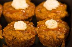 Εύγευστα καφετιά χρωματισμένα muffins που παρατάσσονται με το κάλυμμα καραμέλας και κρέμας, όπως βλέπω? άνωθεν γωνία, έννοια ζύμη Στοκ φωτογραφία με δικαίωμα ελεύθερης χρήσης