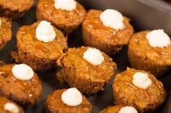 Εύγευστα καφετιά χρωματισμένα muffins που παρατάσσονται με το κάλυμμα καραμέλας και κρέμας, όπως βλέπω? άνωθεν γωνία, έννοια ζύμη Στοκ Φωτογραφίες