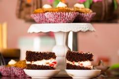 Εύγευστα κομμάτια κέικ σοκολάτας με τη γεμίζοντας συνεδρίαση κρέμας στα μικρά πιάτα, έννοια ζύμης Στοκ Φωτογραφία
