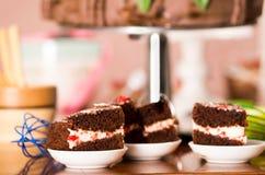 Εύγευστα κομμάτια κέικ σοκολάτας με τη γεμίζοντας συνεδρίαση κρέμας στα μικρά πιάτα, έννοια ζύμης Στοκ Εικόνες