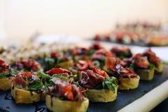 Εύγευστα μικρά σάντουιτς με το μπέϊκον, τις φράουλες και τα πράσινα Στοκ Φωτογραφία