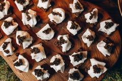 Εύγευστα σάντουιτς με το μαύρα χαβιάρι και το τυρί σε μια ξύλινη τοπ άποψη πινάκων στοκ φωτογραφίες