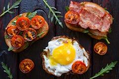 Εύγευστα σάντουιτς σε ένα μαύρο υπόβαθρο που διακοσμείται με τις ψημένες ντομάτες Στοκ Εικόνα