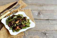 Εύγευστα τηγανισμένα πράσινα φασόλια με τα μανιτάρια και καρυκεύματα σε ένα πιάτο και στο παλαιό ξύλινο υπόβαθρο με το διάστημα α Στοκ φωτογραφίες με δικαίωμα ελεύθερης χρήσης