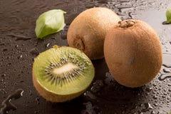 Εύγευστα φρέσκα φρούτα ακτινίδιων με τα φύλλα βασιλικού Στοκ Εικόνα