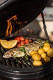 Εύγευστα ψάρια πεστροφών ουράνιων τόξων με τις ντομάτες, τις πατάτες και το μαγείρεμα λεμονιών στην καυτή φλεμένος σχάρα σχάρα Εσ Στοκ Εικόνες