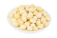 Εύγευστα macadamia καρύδια στο πιάτο στο ξύλινο υπόβαθρο Στοκ Φωτογραφία
