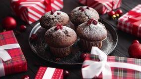 Εύγευστα muffins σοκολάτας Χριστουγέννων που εξυπηρετούνται στο μαύρο κεραμικό πιάτο απόθεμα βίντεο