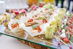 Εύγευστες γαρίδες και τεμαχισμένες ντομάτες σε μια ξύλινη βάρκα Ρόλοι κολοκυθιών με τα καρύδια πεύκων Νόστιμος πίνακας μπουφέδων  στοκ φωτογραφία με δικαίωμα ελεύθερης χρήσης