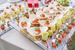 Εύγευστες γαρίδες και τεμαχισμένες ντομάτες σε μια ξύλινη βάρκα Ρόλοι κολοκυθιών με τα καρύδια πεύκων Νόστιμος πίνακας μπουφέδων  στοκ εικόνες με δικαίωμα ελεύθερης χρήσης