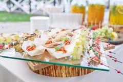 Εύγευστες γαρίδες και τεμαχισμένες ντομάτες σε μια ξύλινη βάρκα Ρόλοι κολοκυθιών με τα καρύδια πεύκων Νόστιμος πίνακας μπουφέδων  στοκ φωτογραφίες με δικαίωμα ελεύθερης χρήσης