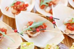 Εύγευστες γαρίδες και τεμαχισμένες ντομάτες σε μια ξύλινη βάρκα Νόστιμος πίνακας μπουφέδων Θερινό κόμμα υπαίθριο Έννοια τομέα εστ στοκ εικόνα