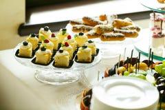 Εύγευστες γλυκές κέικ και ζύμη στον πίνακα γαμήλιων επιδορπίων recep Στοκ Φωτογραφίες