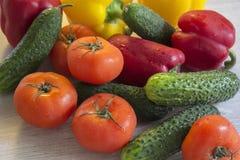 Εύγευστες και ζωηρόχρωμες πιπέρια, αγγούρια και ντομάτες που βρίσκονται επάνω Στοκ εικόνα με δικαίωμα ελεύθερης χρήσης