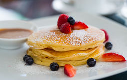 Εύγευστες πρόσφατα έτοιμες τηγανίτες με τη φράουλα και το μέλι Στοκ Φωτογραφίες