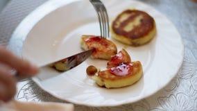 Εύγευστες σπιτικές τηγανίτες τυριών με τη σταφίδα, κόκκινη τρέχουσα μαρμελάδα σε ένα άσπρο πιάτο απόθεμα βίντεο