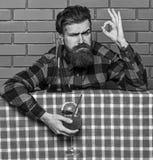 εύγευστη έννοια Άτομο στο ελεγμένο πουκάμισο κοντά στο μπουκάλι, υπόβαθρο τουβλότοιχος Bartender συστήνει να δοκιμάσει το ποτό στοκ εικόνες
