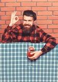 εύγευστη έννοια Άτομο στο ελεγμένο πουκάμισο κοντά στο μπουκάλι, υπόβαθρο τουβλότοιχος Ο μπάρμαν με τη γενειάδα στο εύθυμο πρόσωπ στοκ εικόνες με δικαίωμα ελεύθερης χρήσης