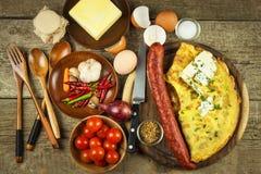 Εύγευστη γεμισμένη ομελέτα σε έναν ξύλινο πίνακα Τηγανισμένη ομελέτα αυγών με τις ντομάτες κερασιών, τα πιπέρια σκόρδου και τσίλι Στοκ Εικόνα