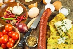 Εύγευστη γεμισμένη ομελέτα σε έναν ξύλινο πίνακα Τηγανισμένη ομελέτα αυγών με τις ντομάτες κερασιών, τα πιπέρια σκόρδου και τσίλι Στοκ Εικόνες