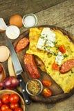 Εύγευστη γεμισμένη ομελέτα σε έναν ξύλινο πίνακα Τηγανισμένη ομελέτα αυγών με τις ντομάτες κερασιών, τα πιπέρια σκόρδου και τσίλι Στοκ φωτογραφίες με δικαίωμα ελεύθερης χρήσης