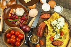 Εύγευστη γεμισμένη ομελέτα σε έναν ξύλινο πίνακα Τηγανισμένη ομελέτα αυγών με τις ντομάτες κερασιών, τα πιπέρια σκόρδου και τσίλι Στοκ εικόνες με δικαίωμα ελεύθερης χρήσης