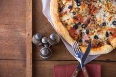 Εύγευστη ιταλική πίτσα με pepperoni το λουκάνικο, ζαμπόν, ελιά, basi Στοκ Εικόνες