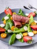 Εύγευστη ιταλική σαλάτα με τα πράσινα, τις φράουλες, το bresaola, τα κομμάτια και τη μοτσαρέλα r o στοκ φωτογραφίες με δικαίωμα ελεύθερης χρήσης