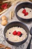 Εύγευστη και υγιής ζωή προγευμάτων ακόμα με oatmeal και τα φρέσκα σμέουρα στα καθαρισμένα κύπελλα Στοκ Φωτογραφία