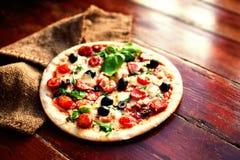 Εύγευστη καυτή πίτσα με το σαλάμι, pepperoni και το τυρί σε ένα σκοτάδι Στοκ εικόνες με δικαίωμα ελεύθερης χρήσης