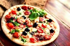 Εύγευστη καυτή πίτσα με το σαλάμι, pepperoni και το τυρί σε ένα σκοτάδι Στοκ Εικόνες