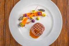 Εύγευστη μπριζόλα βόειου κρέατος με τη σάλτσα και το λαχανικό, που εξυπηρετούνται στο άσπρο πιάτο, τη σύγχρονη γαστρονομία, εστια στοκ εικόνες με δικαίωμα ελεύθερης χρήσης