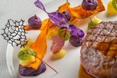 Εύγευστη μπριζόλα βόειου κρέατος με τη σάλτσα και το λαχανικό, που εξυπηρετούνται στο άσπρο πιάτο, τη σύγχρονη γαστρονομία, εστια στοκ φωτογραφία